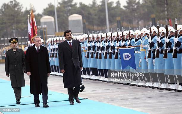 Qatari Crown Prince Sheikh Tamim bin Hamad bin Khalifa alThani and Turkish President Recep Tayyip Erdogan walk past a guard of honor during an...