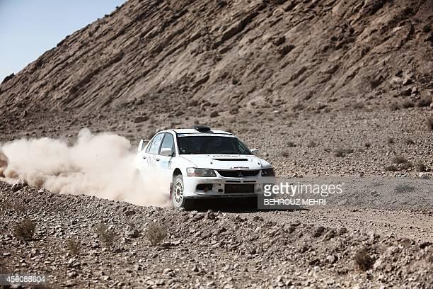 Qatari driver Khalifa Saleh alAttiyah and his Cypriot codriver Savvas Laos of QMMF rally Team drive their Mitsubishi Lancer EVO VII during the FIA...