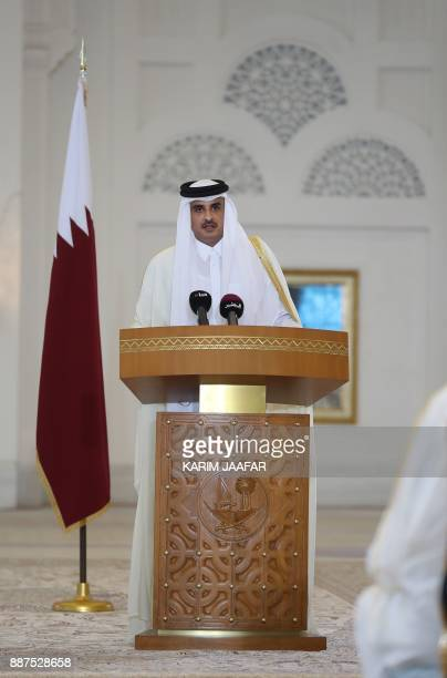 Qatari Emir Sheikh Tamim bin Hamad alThani delivers a speech during a press conference with the French president following the signing of agreements...