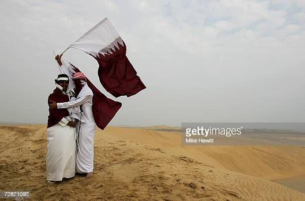 Qatari fans wave a flag at the Equestrian Endurance Event at the Mesaieed Endurance Course 15th Asian Games Doha 2006 on December 14 2006 in Doha...