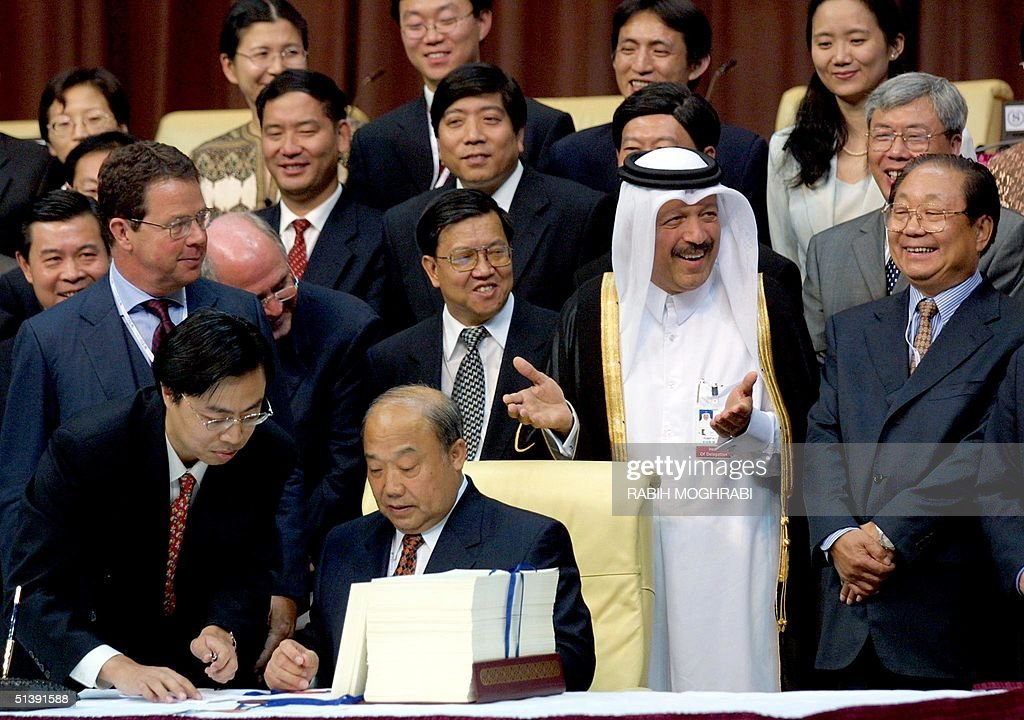 Qatari Finance Economy and Trade Minister Sheikh Yussef Hussein Kamal gestures as he shares a light moment with an unidentified Chinese delegates...