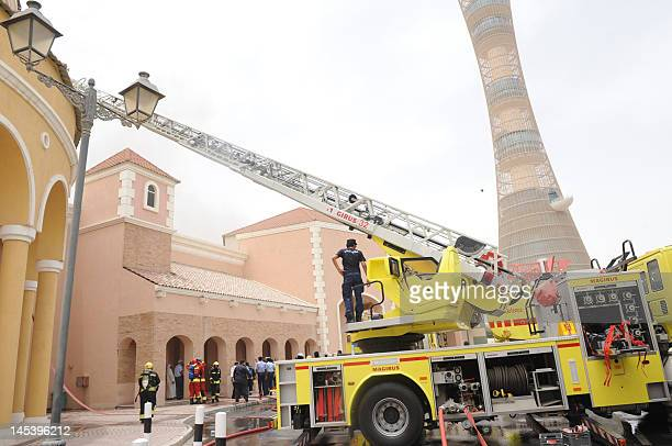 Qatari firefighters and rescue teams work outside Doha's Villagio Mall after a fire broke out at the Gulf emirate's main shopping centre on May 28...