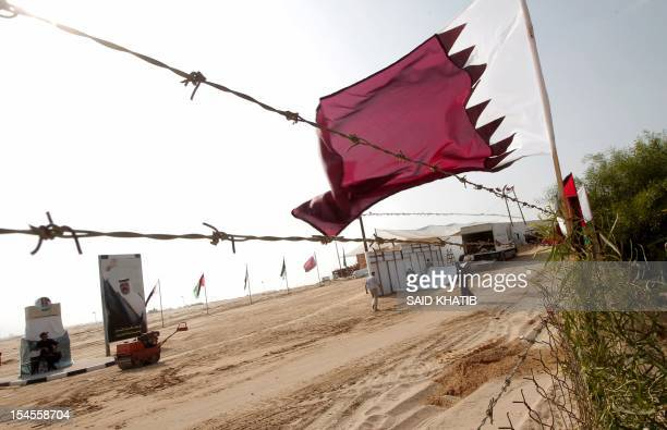 A Qatari flag flutters near a poster of Qatar's Emir Sheikh Hamad bin Khalifa alThani at the construction site of a residential project funded by...