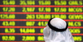 A Qatari investor follows the stock market activity at the Doha Securities Market as the index surged on December 5 the first trading day after the...