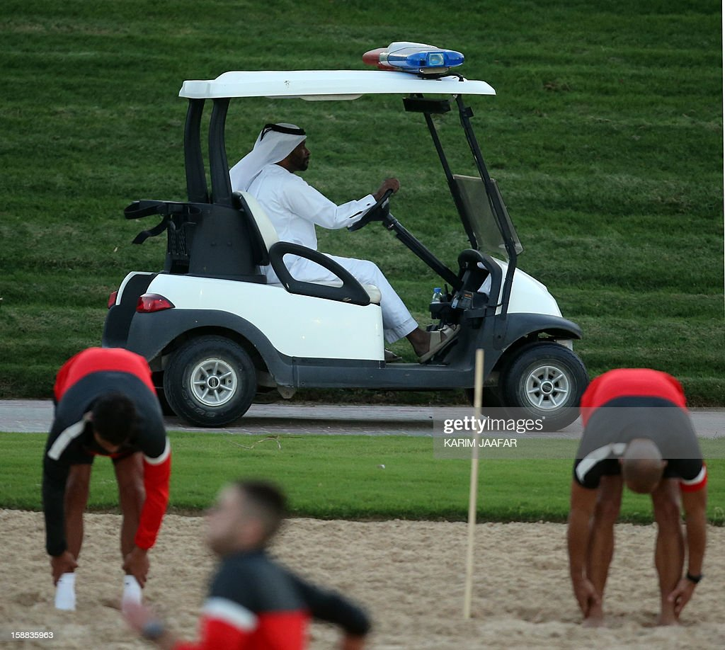 A Qatari man drives a golf buggy past Paris Saint-Germain football players training at the Aspire Academy of Sports Excellence in the Qatari capital Doha on December 31, 2012. PSG is in Qatar for a week-long training camp before the resumption of the French Ligue 1 after the winter break. AFP PHOTO / AL-WATAN DOHA / KARIM JAAFAR == QATAR OUT ==