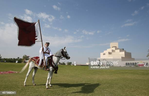 A Qatari man riding a horse poses with his national flag near the Qatar Islamic Museum during celebrations marking the Gulf emirate's national day in...