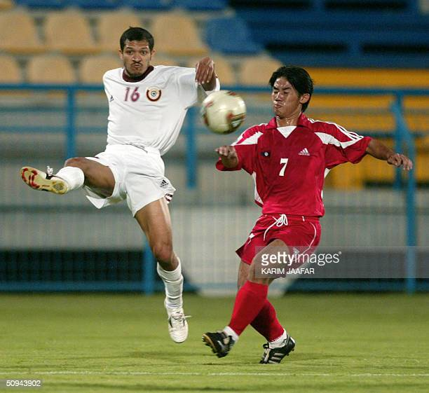 Qatari Mohammed Ghulam fights for the ball against Valasine Dalaphone of Laos during their 2006 World Cup Asian zone qualifying match in Doha 09 June...