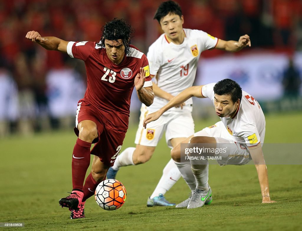 Qatari player Sebastian Soria dribbles past Chinese player Zhang Linpeng during the AFC qualifying football match for the 2018 FIFA World Cup between...