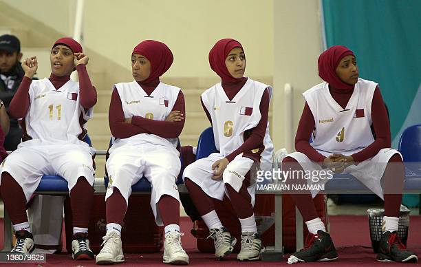 Qatari players wearing Islamic sportswear especially designed for women sit on the bench during their 2011 Arab Games basketball match against...