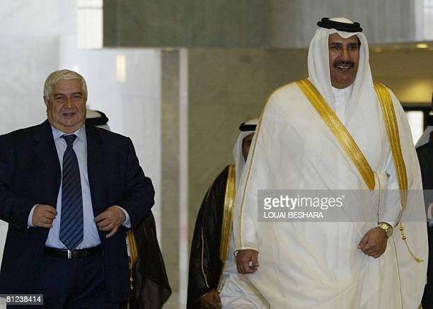 Qatari Prime Minister Sheikh Hamad bin Jassem bin Jabr alThani is escorted by Syrian Foreign Minister Walid Muallem upon his arrival at the...