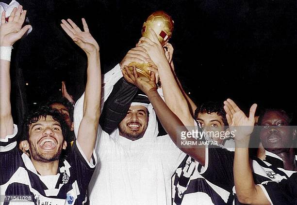 Qatari Sheikh Tamim bin Hamad alThani son of the Qatari Emir and president of the alSaad soccer club holds up the winning trophy surrounder by alSaad...
