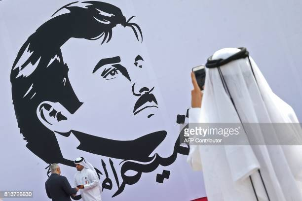 Qatari takes a photo during the inaugural signing of a wall bearing a portrait of Qatar's Emir Sheikh Tamim bin Hamad alThani in Doha on July 13 2017...