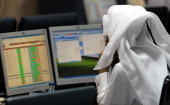 A Qatari trader follows the stock market activity at the Doha Securities Market as the index surged on December 5 the first trading day after the...
