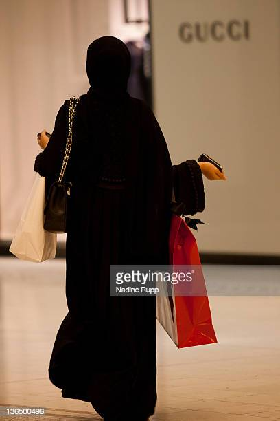 Qatari woman in her traditional clothes called abaya shops at the luxury part of Villagio shopping mall on December 25 2011 in Doha Qatar The The...