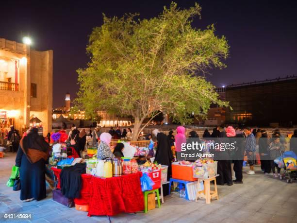 Qatari women making and selling traditional foods in souq waqif at night, Doha, Qatar - February 3, 2017