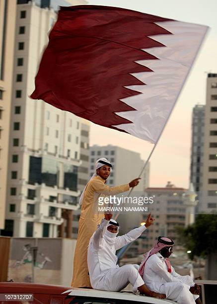 Qataris wave their national flag as they celebrate in Doha on December 3 2010 a day after the world football's governing body FIFA announced that the...