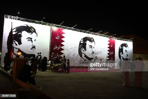 Qataris write comments on a wall bearing a portrait of Qatar's Emir Sheikh Tamim bin Hamad Al Thani which has become the symbol of Qatari resistance...