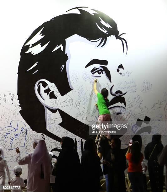Qataris write comments on a wall bearing a portrait of Qatar's Emir Sheikh Tamim bin Hamad Al Thani in Doha on July 6 2017 / AFP PHOTO / KARIM JAAFAR