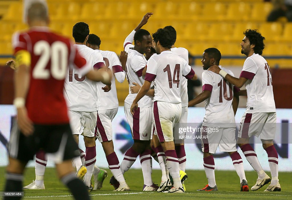 Qatar's Abdul Karim Hasan (C) is congratulated by teammates after scoring a first goal during the friendly football match Qatar versus Egypt in the Qatari capital Doha on March 7, 2013. The match comes in the frame of the both national teams preparation for Asian and African qualification rounds for FIFA 2014 World Cup Finals in Brazil.