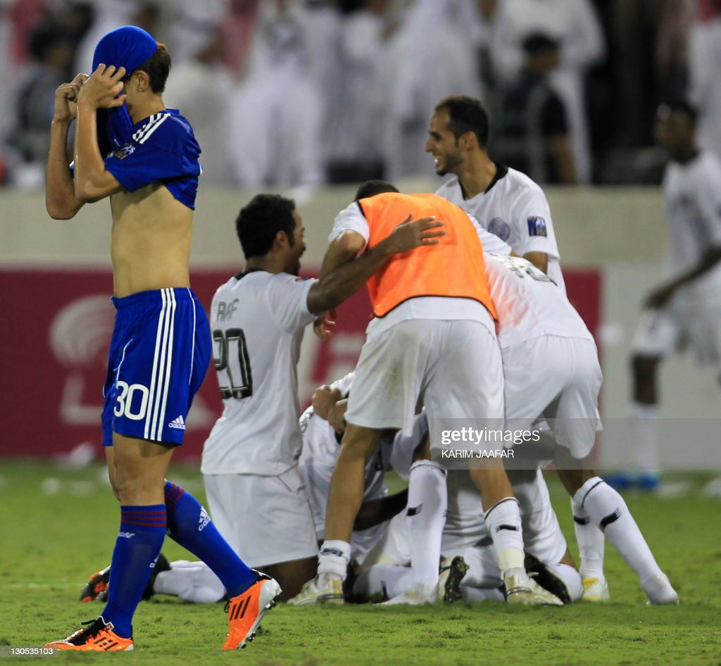 Qatar's Al Sadd players celebrate after their match against South Korea's Suwon Samsung Bluewings while Sin Se Gye (L) reacts during their semi-final football match in the AFC Champions League in Doha, on October 26, 2011. Suwon Samsung Bluewings won the match 1-0.