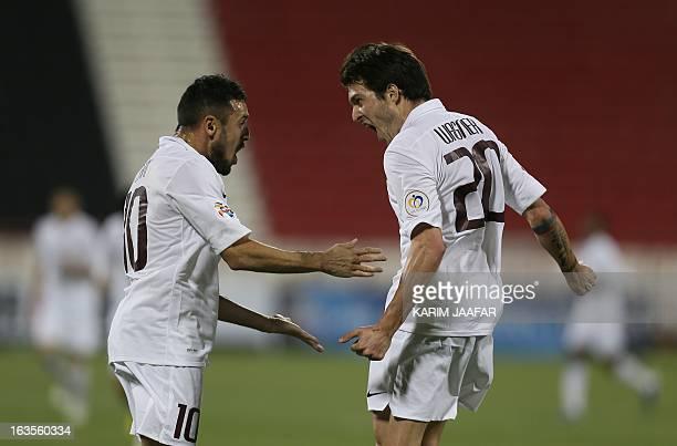 Qatar's AlJaish players Wagner Renan Ribeiro celebrates with his teammate player Karim Ziani after scoring a goal against Iran's Teraktor Sazi Tabriz...