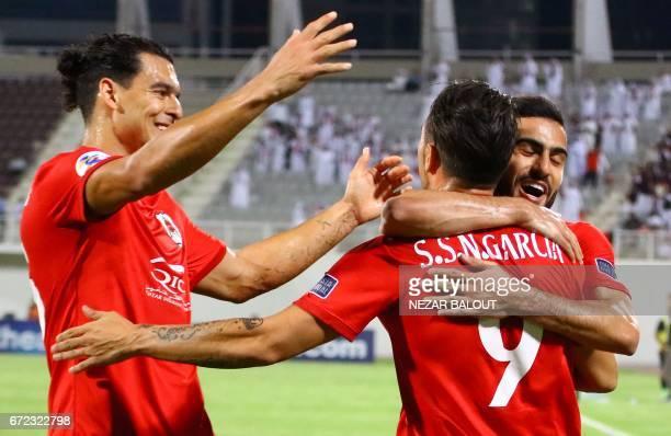 Qatar's AlRayyan SC player Sergio Garcia celebrates scoring a goal against UAE's AlWahda with teammates Abdulkarim AlAli and Sebastian Soria during...