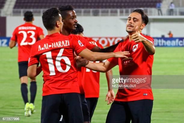Qatar's AlRayyan SC player Sergio Garcia celebrates scoring a goal against UAE's AlWahda with his teammates Abdurahman AlHarazi and Musab Kheder...