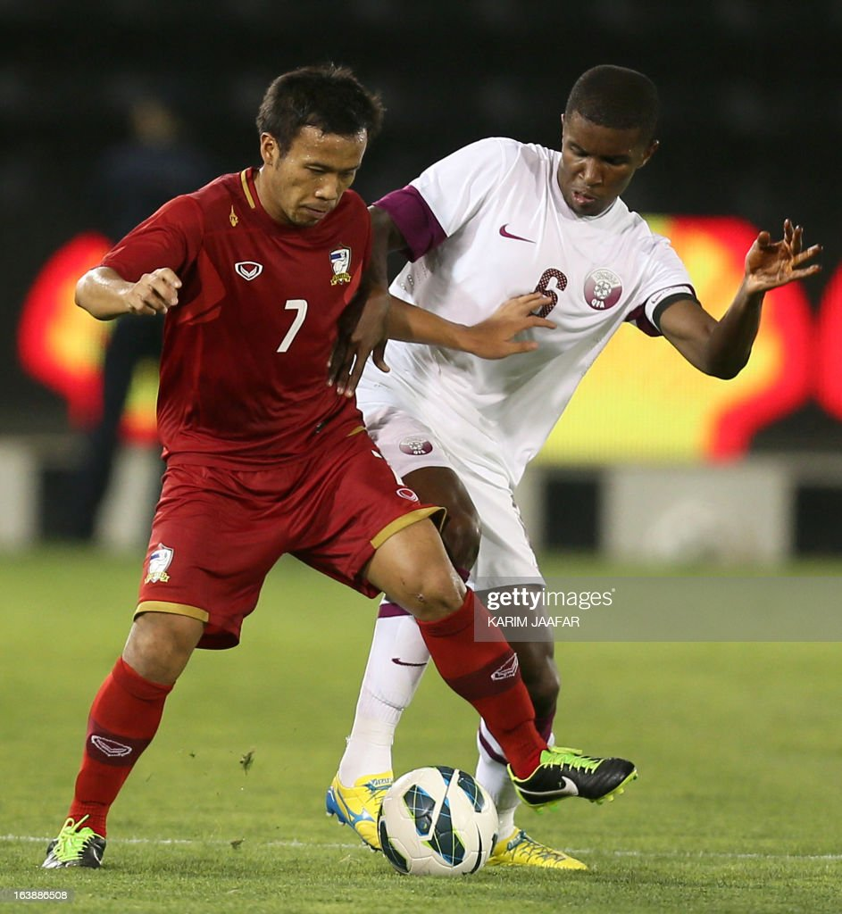 Qatar's Bilal Mohammed (R) vies for the ball with Thailand's Datsakom Thonglao during their friendly football match in the Qatari capital Doha on March 17, 2013.