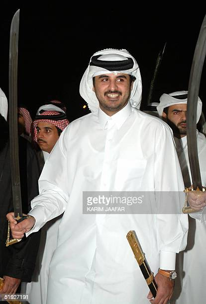 Qatar's Crown Prince Sheikh Tamim bin Hamad alThani holds a sword during a traditional ceremony marking his wedding 08 January 2005 in Doha The Gulf...