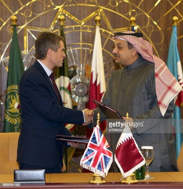 Qatar's Defence Minister Khalid bin Mohammed alAttiyah exchanges documents with his British counterpart Gavin Williamson in the capital Doha on...