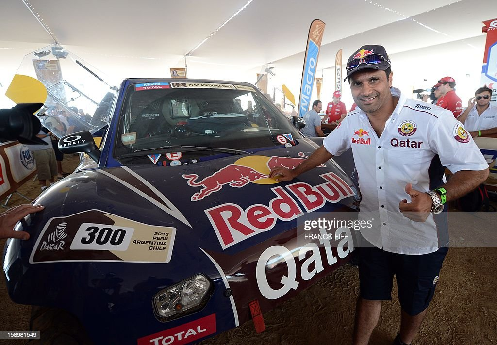 Qatar's driver Nasser Al-Attiyah poses in front of his buggy in Lima on January 4, 2013, ahead of the 2013 Dakar Rally which this year will thunder through Peru, Argentina and Chile from January 5 to 20. AFP PHOTO / FRANCK FIFE