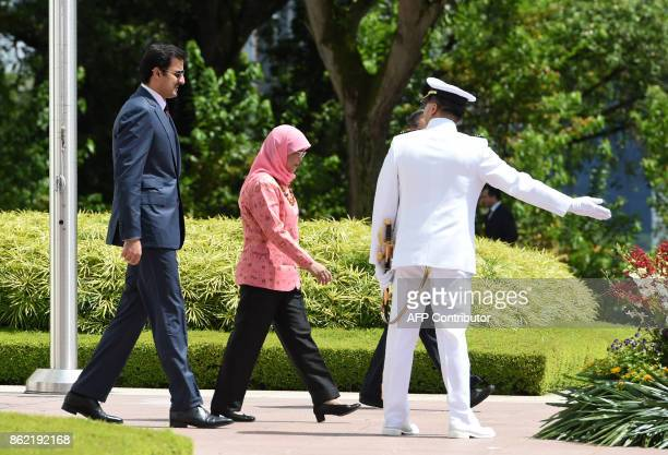 Qatar's Emir Sheik Tamim bin Hamad alThani and Singapore President Halimah Yacob arrive for the welcoming ceremony at the Istana presidential palace...