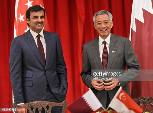 Qatar's Emir Sheik Tamim bin Hamad alThani and Singapore Prime Minister Lee Hsien Loong arrive to witness the signing ceremony of Memorundum of...