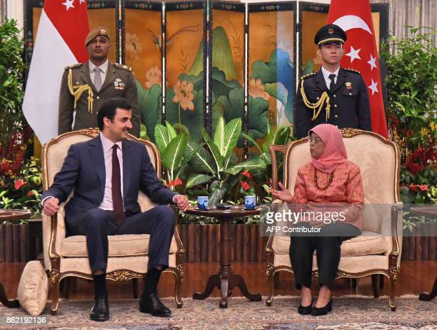 Qatar's Emir Sheik Tamim bin Hamad alThani meets with Singapore President Halimah Yacob at the Istana presidential palace on October 17 2017 Qatar's...