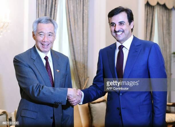 Qatar's Emir Sheik Tamim bin Hamad alThani shakes hands with Singapore Prime Minister Lee Hsien Loong at the Istana presidential palace on October 17...