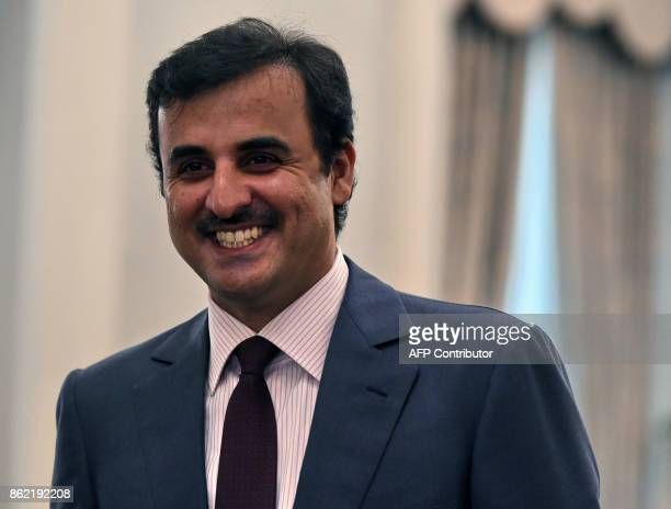 Qatar's Emir Sheik Tamim bin Hamad alThani smiles after a welcoming ceremony at the Istana presidential palace on October 17 2017 Qatar's Emir Sheik...