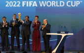 Qatar's Emir Sheikh Hamad bin Khalifa alThani raises the World Cup trophy as he stands with his wife Sheikha Moza their son Sheikh Mohammed chairman...