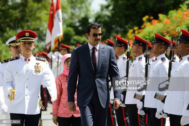 Qatar's Emir Sheikh Tamim bin Hamad alThani inspects the guard of honour accompanied by Singapore President Halimah Yacob during the welcome ceremony...
