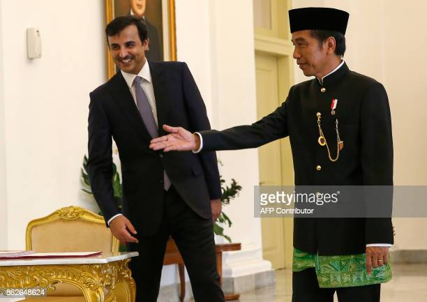 Qatar's Emir Sheikh Tamim Bin Hamad alThani is welcomed by Indonesian President Joko Widodo during his arrival at the presidential palace in Bogor...