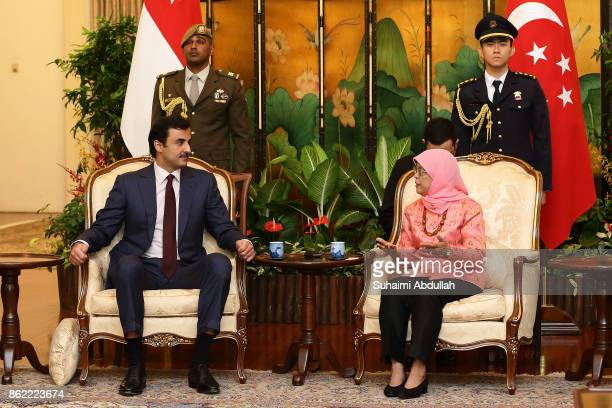 Qatar's Emir Sheikh Tamim bin Hamad alThani meets with Singapore President Halimah Yacob at the Istana on October 17 2017 in Singapore It is the...