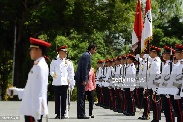 Qatar's Emir Sheikh Tamim bin Hamad alThani pays respect to the ceremonial flag accompanied by Singapore President Halimah Yacob during the welcome...