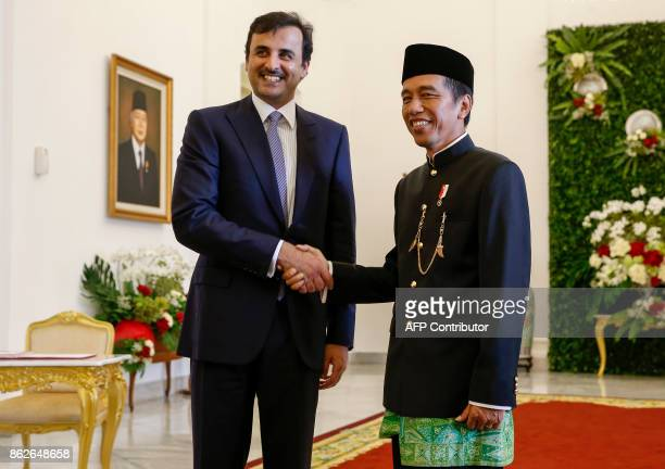 Qatar's Emir Sheikh Tamim Bin Hamad alThani shakes hands with Indonesian President Joko Widodo during his arrival at the presidential palace in Bogor...