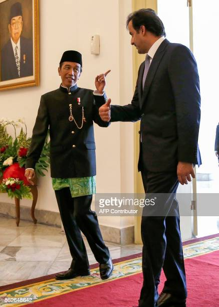 Qatar's Emir Sheikh Tamim Bin Hamad alThani talks to Indonesian President Joko Widodo during his arrival at the presidential palace in Bogor West...