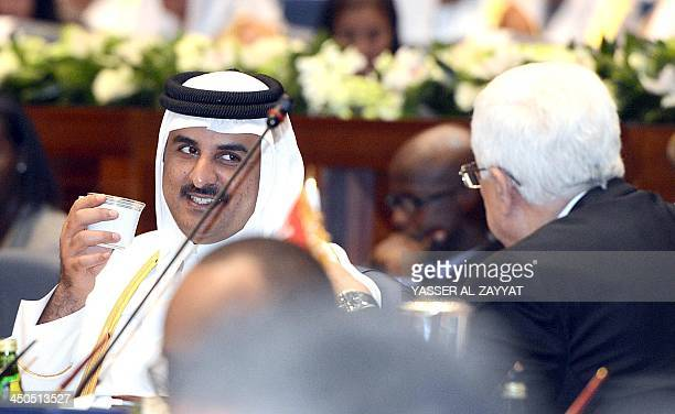 Qatar's Emir Shiekh Tamim bin Hamad alThani listens to Palestinian president Mahmud Abbas during an Arab and African leaders summit meeting in Kuwait...