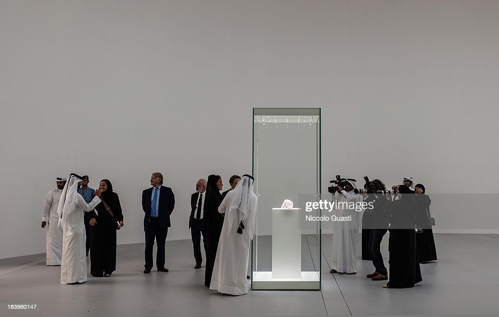 Qatar's First Lady Sheikha Mozah bint Nasser al-Missned observes 'For the love of God' artworks (a skull made of diamonds) by Damien Hirst on October 9, 2013 in Doha, Qatar.