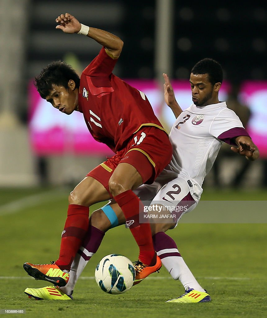 Qatar's Hamed Ismail (R) vies for the ball with Thailand's Anucha Kitpongsri during their friendly football match in the Qatari capital Doha on March 17, 2013.