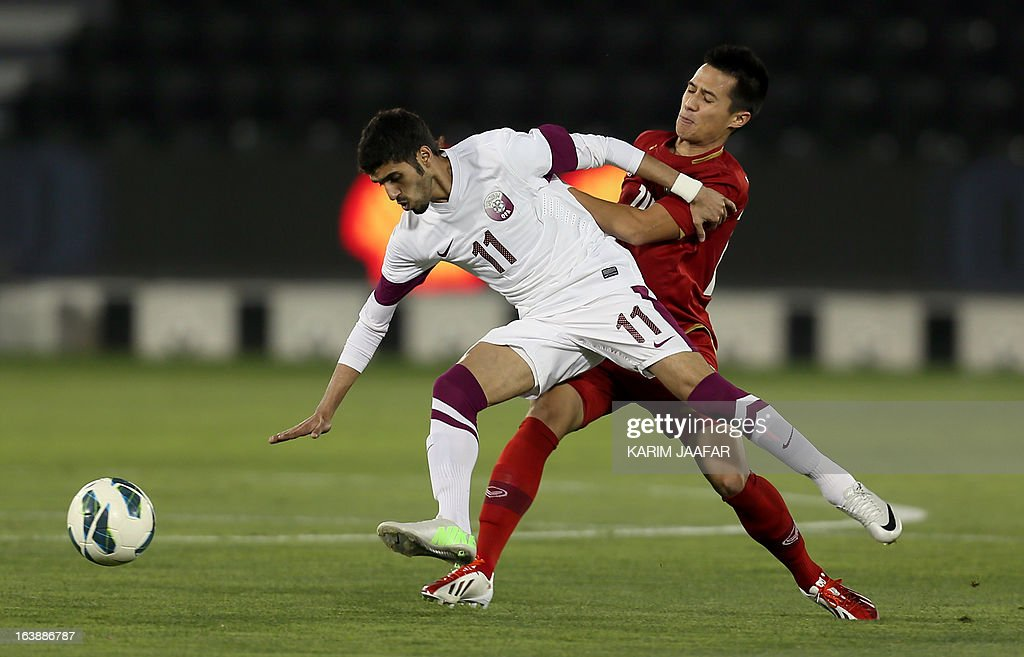Qatar's Hasan al-Haidous (L) vies for the ball with Thailand's Anthony Ampaipitakwong during their friendly football match in the Qatari capital Doha on March 17, 2013.