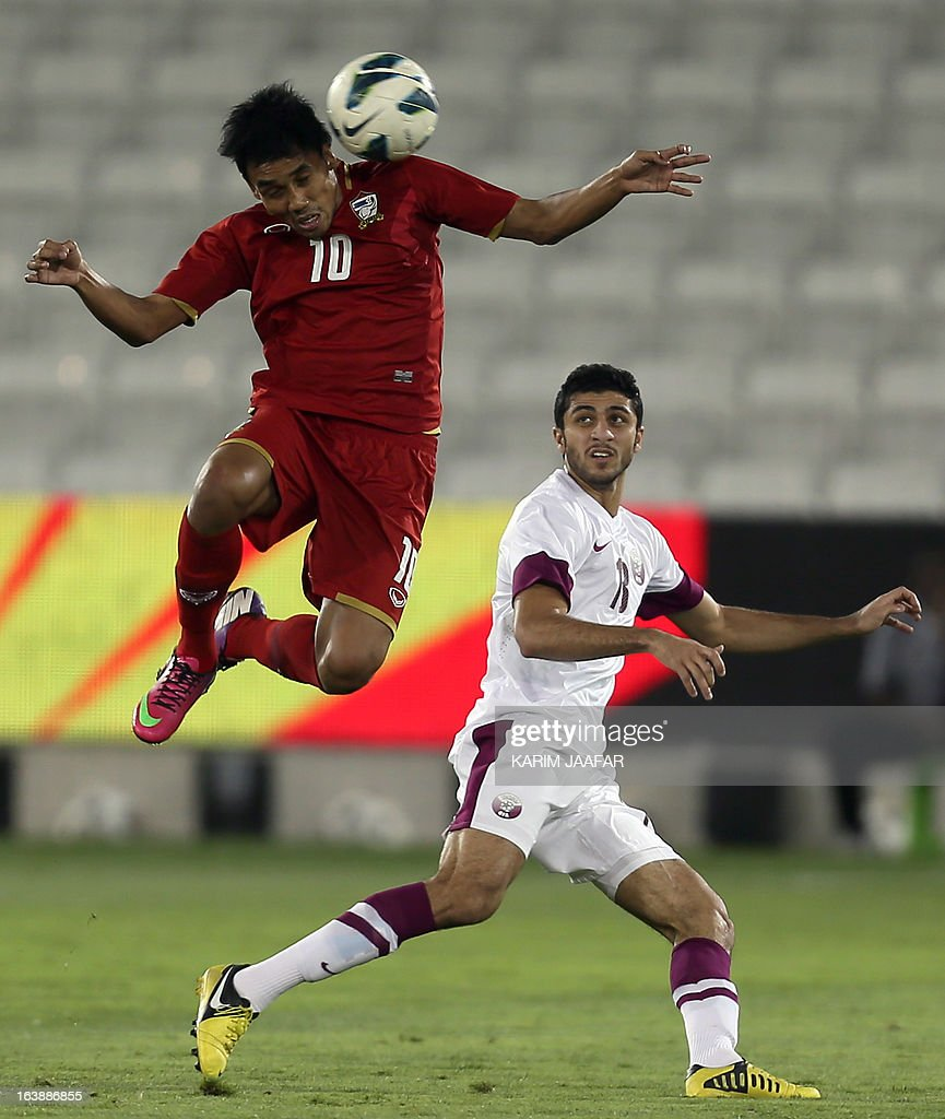 Qatar's Ibrahim Maged (R) vies for the ball with Thailand's Terrasil Dangda during their friendly football match in the Qatari capital Doha on March 17, 2013.