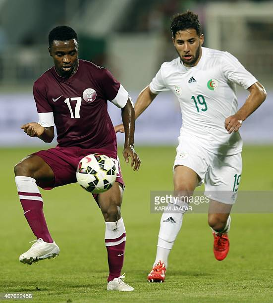 Qatar's Ismail Mohammed controls the ball under pressure from Algeria's Saphir Taïder during the friendly football match between Qatar and Algeria at...