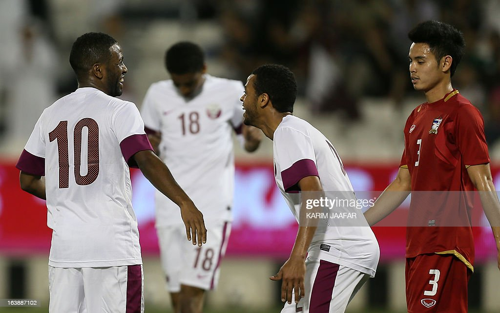 Qatar's Khalfan Ibrahim (L) celebrates with teammates after scoring a goal against Thailand during their friendly football match in the Qatari capital Doha on March 17, 2013.
